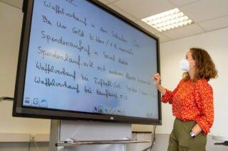 Lehrerin Caroline Werner sammelt die Vorschläge aus der Kasse FHR 11c für Spendenaktionen. Foto: SMMP/Ulrich Bock