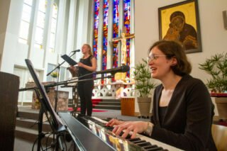 Musiklehrerin Lisa Kuckhoff (vorne) und Schülerin Sophie Hermann gestalten den Abschlussgottesdienst musikalisch mit Gesang und Klavierbegleitung. Foto: SMMP/Ulrich Bock